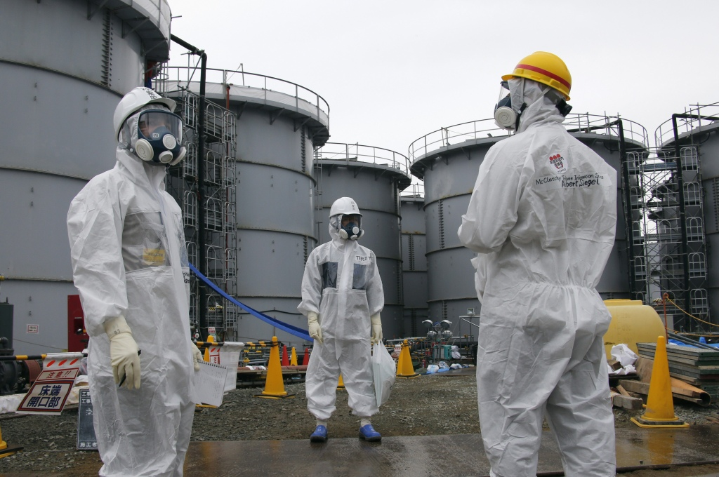 TEPCO official and journalists wearing protective suits and masks stand in front of storage tanks for radioactive water in the H4 area, where radioactive water leaked from a storage tank in August, at the TEPCO Fukushima Daiichi nuclear power plant