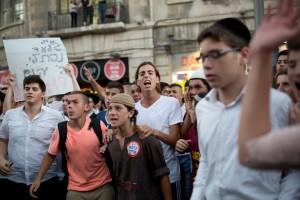 """Lors d'une manifestation de la droite à Jérusalem, une pancarte lit """"Puisse Dieu venger leur sang"""" et un jeune porte un autocollant qui lit, """"Kahane avait raison"""", en référence au leader violent du mouvement des colons né à Brooklyn, la 1 juillet - Tali Mayer / Active Stills"""
