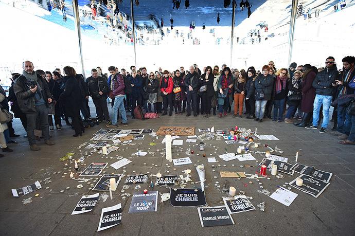 """Des gens sont rassemblés près d'affiches lisant """"je suis Charlie"""" et des bougies placées sur le sol, après avoir observé une minute de silence au Vieux Port de Marseille le 8 janvier 2015, en hommage aux victimes d'une attaque par des hommes armés aux bureaux du journal satyrique français Charlie Hebdo à Paris le 7 janvier 2015 - Photo AFP/Anne-Christine Poujoulat"""