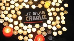 """Des bougies sont placées près d'une affiche lisant """"Je suis Charlie"""" et un crayon à La Rochelle le 7 janvier 2015, alors que les gens se sont rassemblés pour rendre hommage aux douze personnes tuées lors d'une attaque par deux hommes armés aux bureaux du journal satyrique français Charlie Hebdo, à Paris - Photo AFP/Xavier Leoty"""