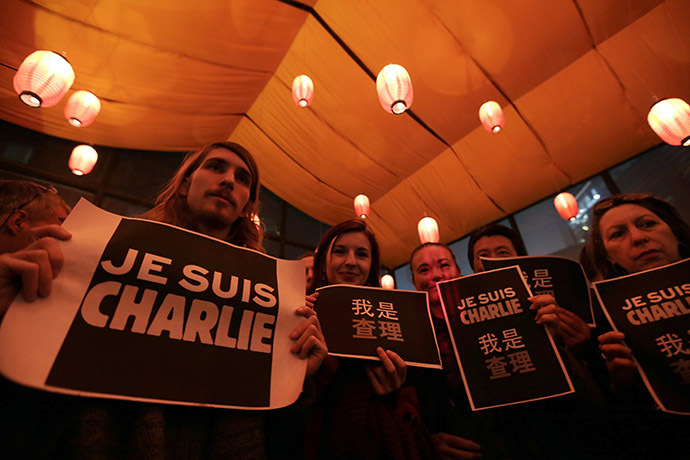 "Foreign journalists and other people hold placards that read ""I am Charlie"" during a campaign at a bookstore in Beijing"