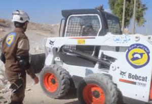 """Du matériel """"made in USA"""": les casques Blancs étrennent leur pelleteuse Bobcat (entreprise US) toute neuve à Idlib, à la frontière turque - capture d'écran d'une vidéo promotionnelle des Casques Blancs"""
